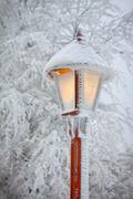 Bright shining snowy street lamp - stock photo