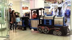 Train passing by stores for holiday season game inside shopping mall Stock Footage