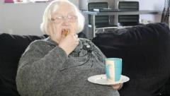 Old, senior woman is sitting on a sofa with a cake and coffee Stock Footage