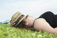 Profile view of woman relaxing on grass - stock photo