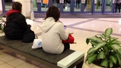 Reading mobile phone message at rest area inside shopping mall entrance Stock Footage