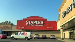 FedEx van delivers to Staples office store Stock Footage
