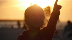 Little Girl Silhouette Points to Something Talking People Families Are Walking Stock Footage