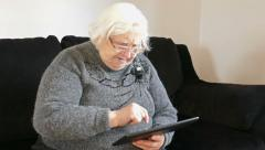 Senior woman is skillfully using tablet computer Stock Footage