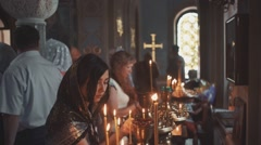 Young female looking at candle flames in church during praying - stock footage