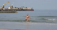 Girl Runs Out From The Water Woman Walks On The Shore Two Barges Work At The Stock Footage