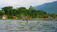 Lake Toba with fishing cages and village in background. 4K resolution. Stock Footage