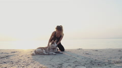 Young sportive female with a husky dog on the beach slow motion Stock Footage