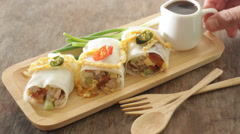 Serving spring rolls with vegetables on wooden plate - stock footage
