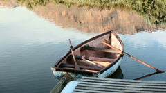 Slow panning shot across battered, old, abandoned rowboat at a dock - stock footage
