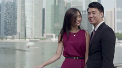 Asian couple in smart clothing turning to smile at the camera Stock Footage
