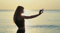 Young sportive female makes selfie on the beach slow motion Stock Footage