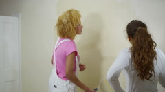 4K Happy young women painting a wall in new home - stock footage
