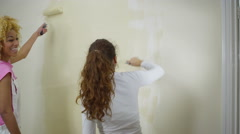 4K Happy young women painting a wall in new home Stock Footage