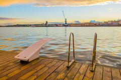 OSLO, NORWAY - 8 JULY, 2015: Diving board mounted on wooden surface above water - stock photo