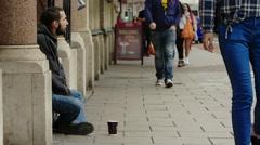 A beggar receiving money from a man Stock Footage