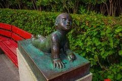 OSLO, NORWAY - 8 JULY, 2015: Sculpture of baby lying using arms to raise upper - stock photo