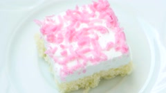 Cake with pink decoration rotates on white plate Stock Footage