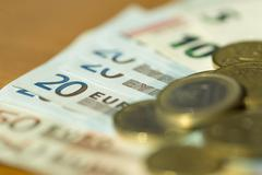 Euro notes and coins strewn across a table with very shallow focus - stock photo