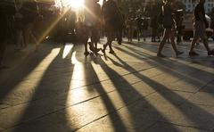 Crowds walking in a district as sun flares between them in the late afternoon Stock Photos