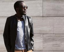 Fashion portrait of stylish young african man wearing a sunglasses and black  - stock photo