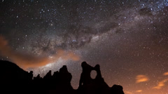 The Milky Way and moon rising over an eroded landscape Stock Footage