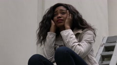 Upset depressed unhappy african girl alone in urban environment. - stock footage