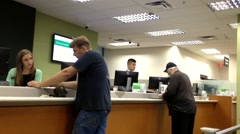 People at service counter talking to the teller Stock Footage