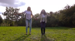 Girls, caucasian and african, having fun outdoors, jumping up, slow motion. - stock footage