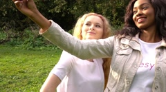 Friends,  girls, caucasian and african, making selfie in park, slow motion. - stock footage