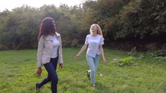 Friends,  girls, caucasian and african, walking, laughing in park, slow motion. Stock Footage