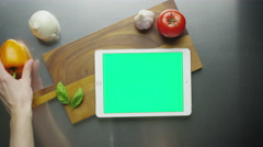 Preparing ingredients on kitchen table with tablet pc in the middle Stock Footage
