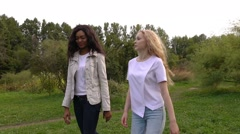 Friends,  girls, caucasian and african, having fun in park, slow motion. Stock Footage