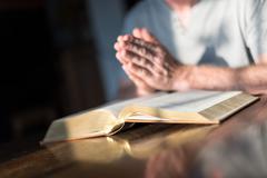 Man praying hands on a Bible - stock photo