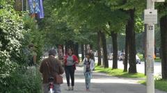Men and women walking near a park in Munich - stock footage