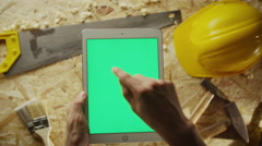Holding tablet pc in portrait mode with carpentry tools in the background Stock Footage