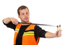 Handsome man concentrated aiming a slingshot with security vest isolated over Stock Photos