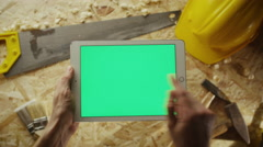 Holding tablet pc in landscape mode with carpentry tools in the background - stock footage