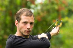 Handsome man concentrated aiming  a slingshot at park having fun - stock photo