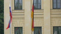 Two flags waving in front of an old building in Munich Stock Footage