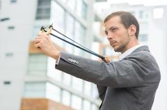 Handsome buisness man concentrated aiming a slingshot at urban city background - stock photo
