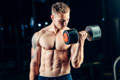 Athlete muscular bodybuilder training back with dumbbell  in the gym Stock Photos