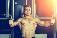 Brutal athletic man pumping up muscles on crossover Stock Photos