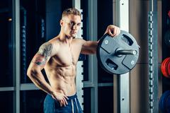Closeup portrait of a muscular man workout with barbell at gym. Brutal - stock photo
