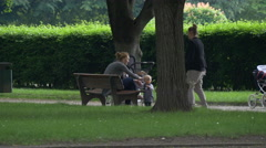 Mother relaxing with her baby boy in the park in Munich Stock Footage