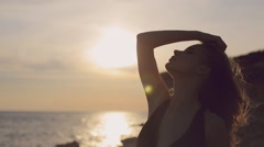 Free girl with flowing hair wearing a dress standing by the sea at sunset on the Stock Footage