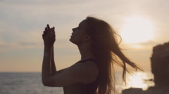 Sensual girl with flowing hair in black dress standing by the sea at sunset Stock Footage