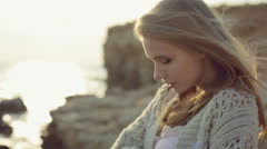 Sensual green-eyed blonde wearing a knitted jacket standing near the sea at Arkistovideo