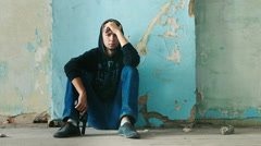 Young man sitting in an abandoned house. The concept of depression, despair Stock Footage