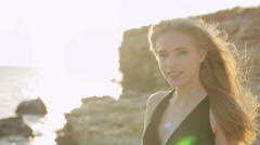 Beautiful blonde with long hair wearing a black dress laughing near the sea at Stock Footage